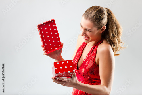 Woman opening the gift and is happy