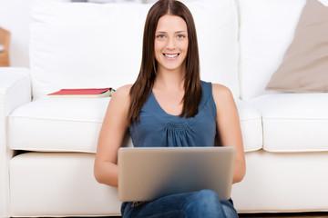 frau sitzt mit laptop vor dem sofa
