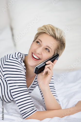 lachendes frau telefoniert auf dem bett