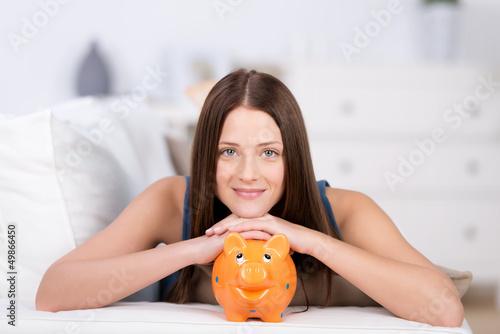 junge frau stützt den kopf auf ein sparschwein