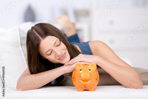 frau schaut zufrieden auf ihr sparschwein