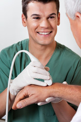 Technician Scanning Male Patient's Hand