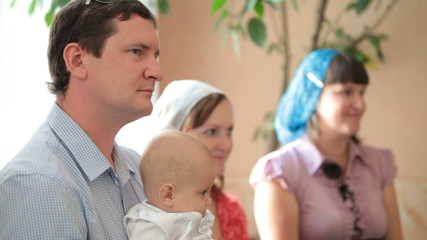 family with a baby on the baptism in the church