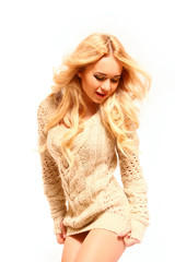 Beautiful blonde woman in a jumper isolated on white background