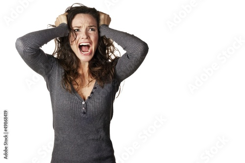 Frustrated and angry woman is screaming and pulling her hair