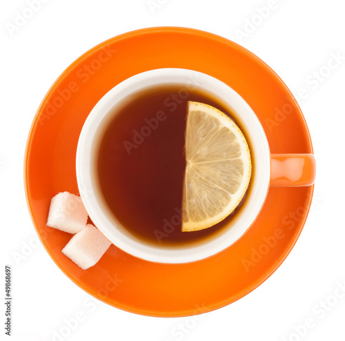 Orange teacup with sugar and lemon.