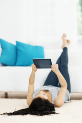 Young woman using tablet on the floor