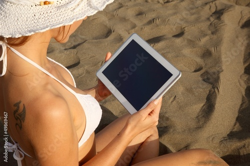 woman at the beach with tablet-pc