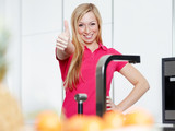 Beautiful woman in kitchen loves cooking, shows thumb up