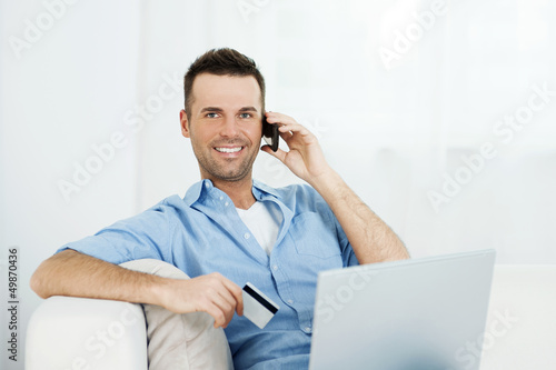 Smiling male shopping via internet.