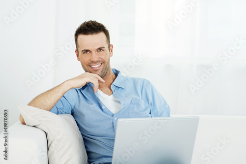 Portrait of handsome man with laptop on sofa