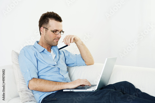 Man using credit card and laptop on couch