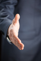 Businessman offering handshake to you - closeup shot