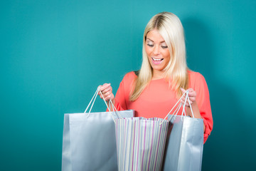 frau schaut glücklich in ihre einkaufstaschen