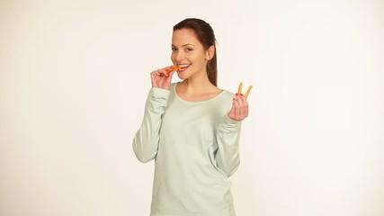 Hübsche junge Frau isst eine Möhre