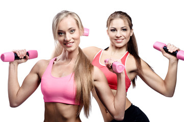 Two beautiful young woman doing fitness exercise with dumbbells