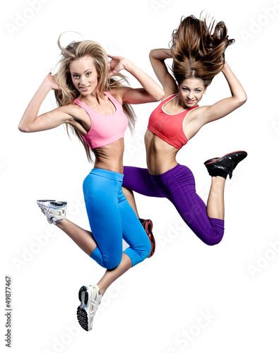 Two beautiful athletic girl jumping over white background