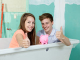 Young couple sit in the bathtub of their site showing thumbs up
