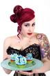 Junge Frau im Pin Up Style serviert Cupcake