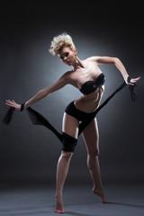 Slim blonde woman in black underwear
