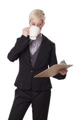 Female office worker sips from coffee cup.