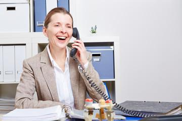 Ältere Frau im Büro telefoniert lachend