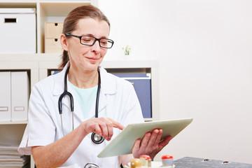 Ärztin in Büro nutzt Tablet Computer