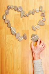 Hand legt Steine zu Herz