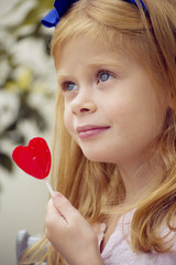 Девочкадержит в руках конфету