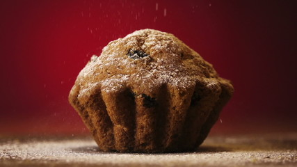Muffin cake with white powdered sugar on red