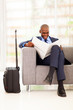 african businessman reading newspaper in airport vip lounge