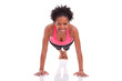 Young beautiful african fitness woman doing push up exercises on