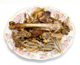 residues from food, bones from fish and chicken on a plate