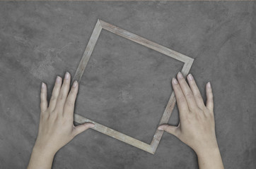 hand holding wooden frame on concrete wall