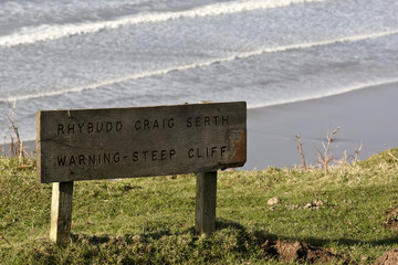 Steep cliff warning sign in English and Welsh