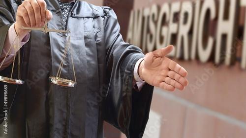 Rechtsanwalt mit Waage vor Gerichtsgebäude