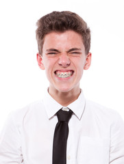 Grimace of teenage boy with braces. Isolated on white background