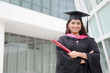young indian female graduate with campus background