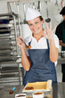 Female Chef Showing Okay Sign In Kitchen