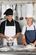 Chefs Kneading Dough In Kitchen