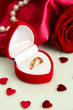 Beautiful box with wedding ring and rose on red silk background
