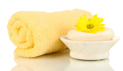Rolled towel, soap bar and beautiful flower isolated on white