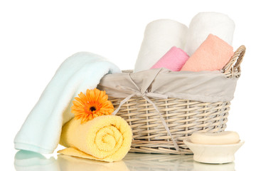 Bathroom towels folded in wicker basket isolated on white