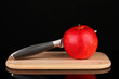 Red apple and knife on cutting board, isolated on black