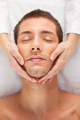 Young man receiving facial massage