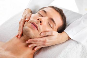 Young man receiving facial massage