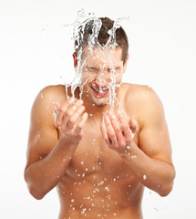 Young man spraying water on his face after shaving