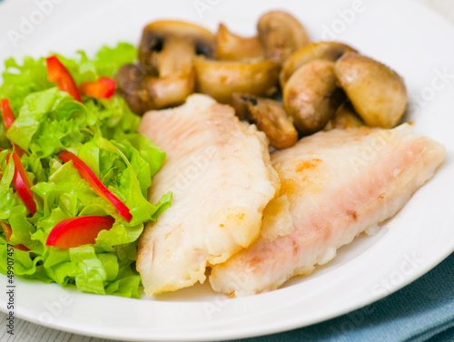 Fish fillet with mushrooms and salad