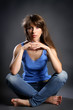 Girl sitting in the lotus position in jeans on a gray