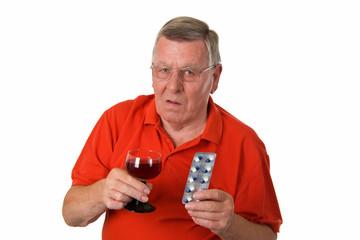 Alter Mann mit Rotwein und Tabletten